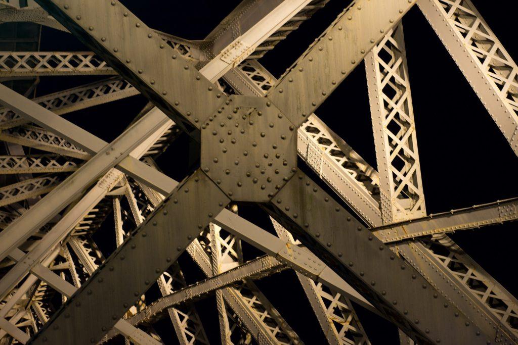 Detailní fotografický záběr na konstrukci mostu focený v noci.